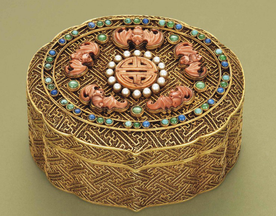A Qianlong [1735-1796] silver-gilt ruyi form box; the lid inset in carved coral bat motifs around a central shou character, mother of pearl and semi-precious stones, all on a filigree geometric ground